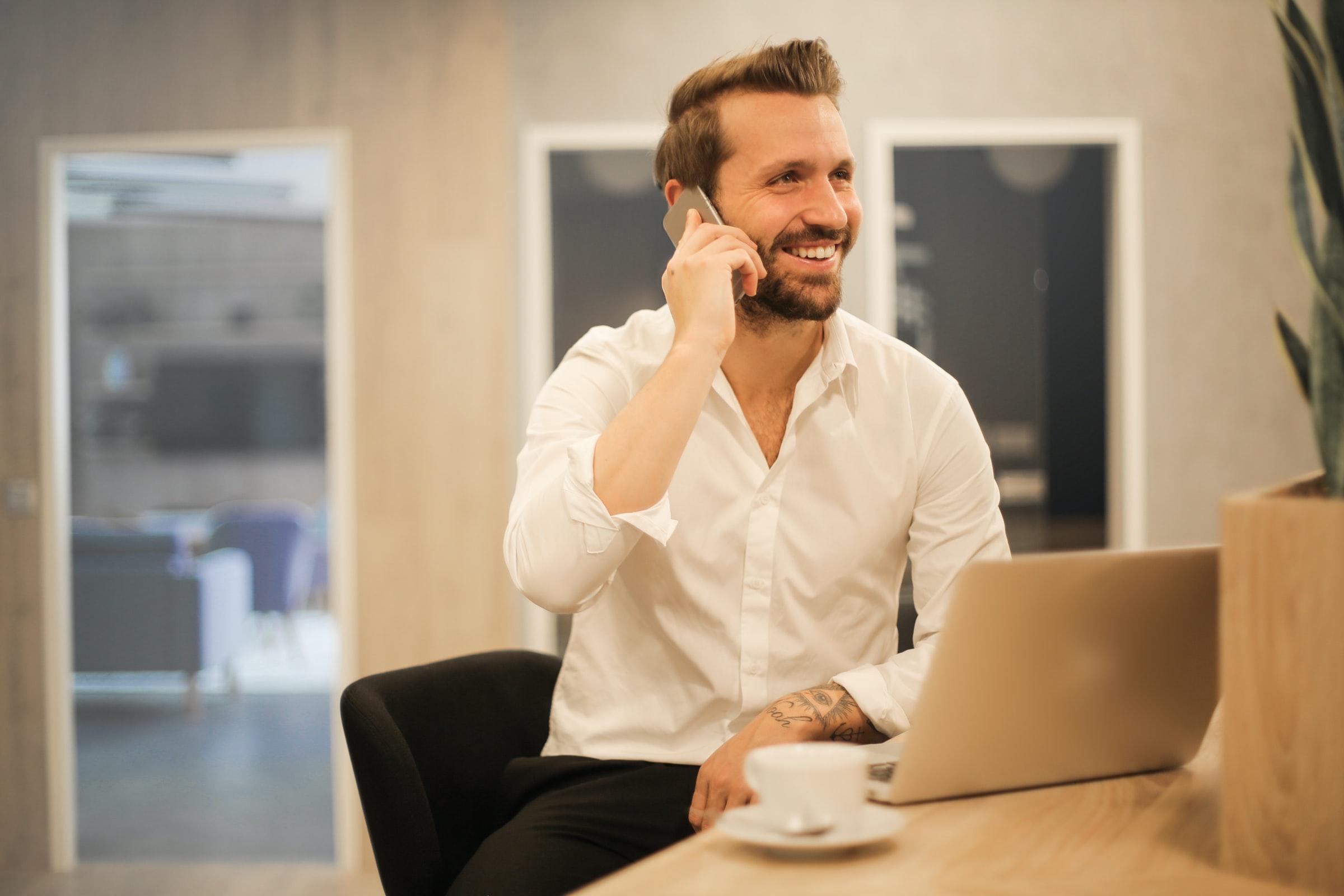 leende man pratar i telefon vid dator