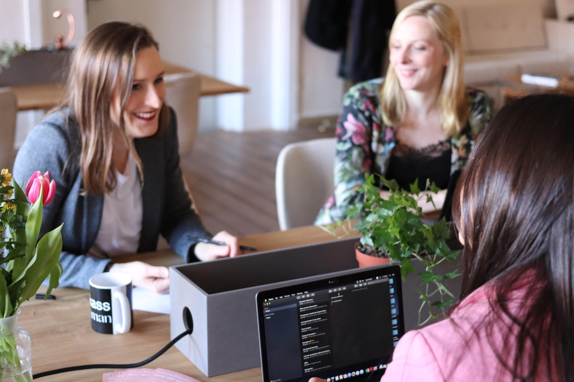tre kvinnor runt konferensbord