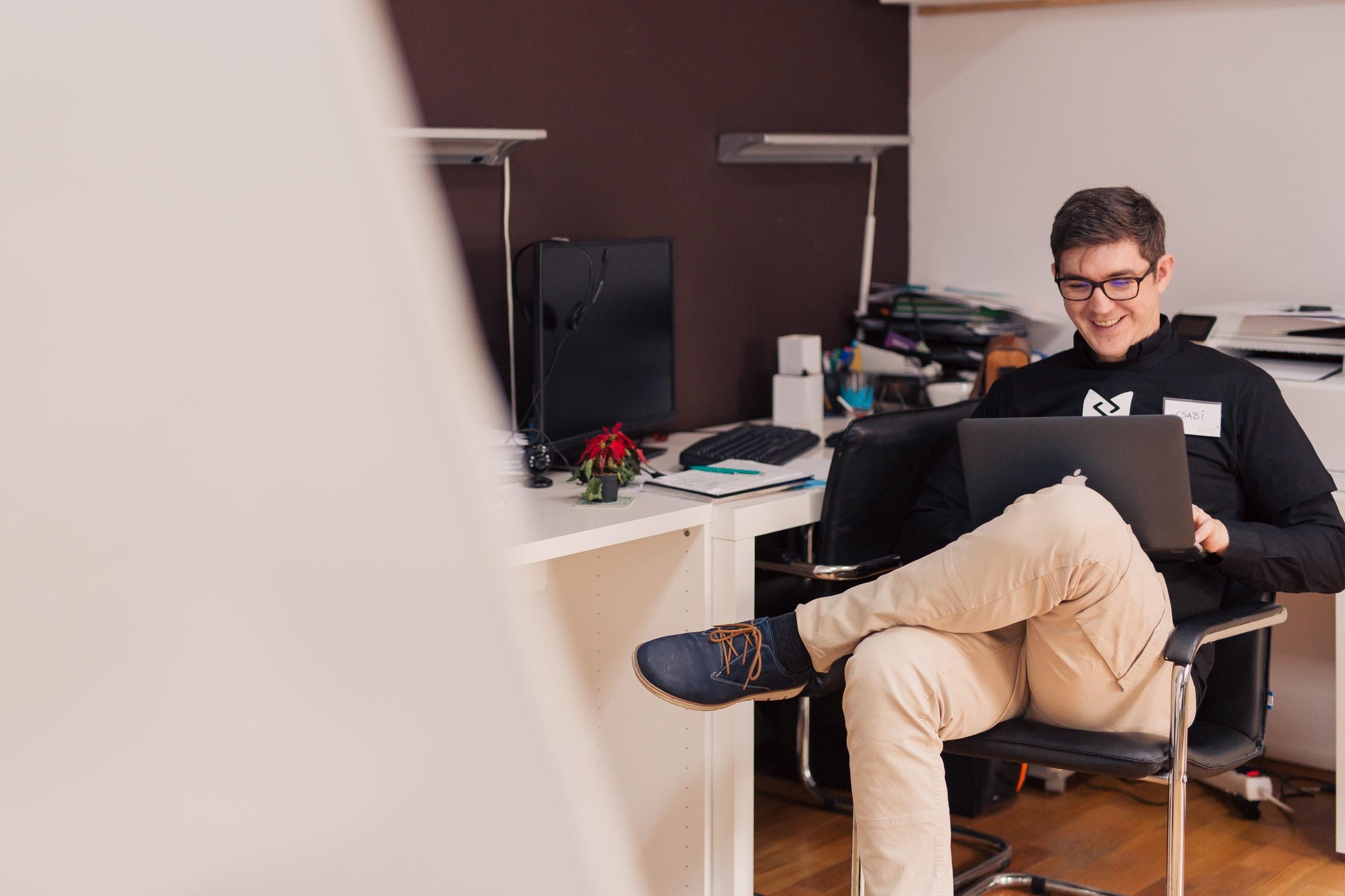 leende man sitter i stol med laptop i knäet