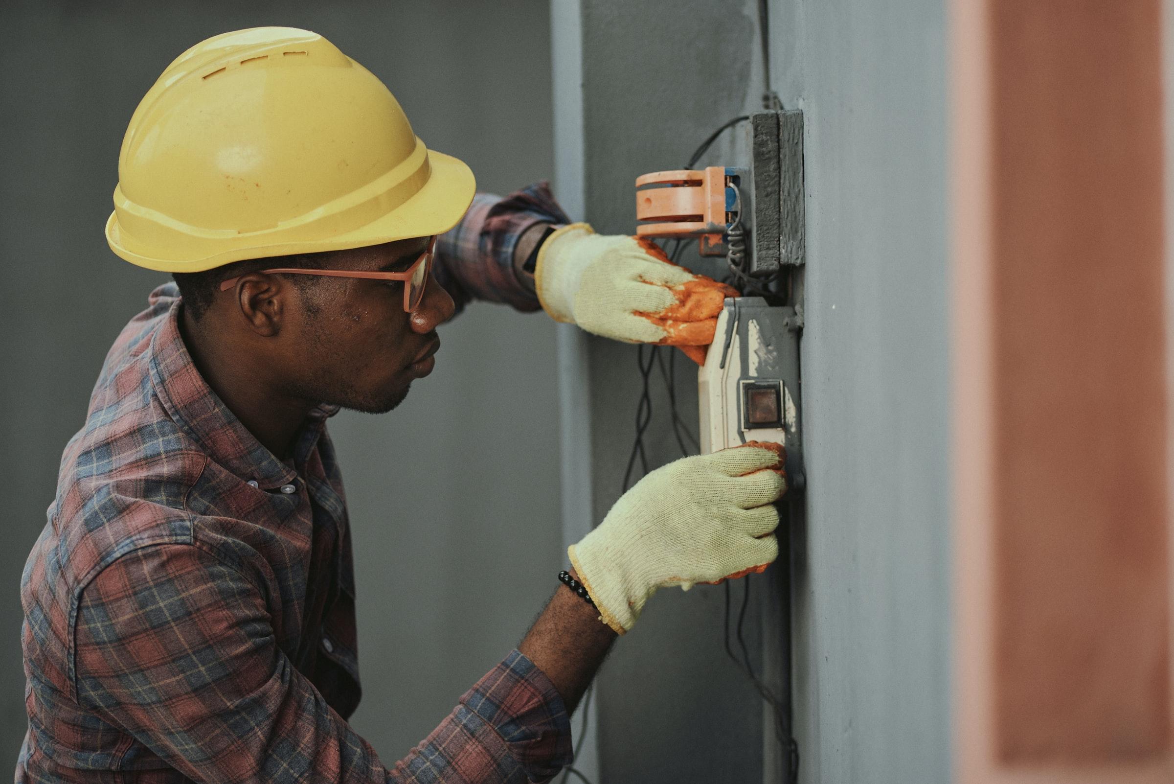 byggarbetare som skruvar fast föremål i vägg