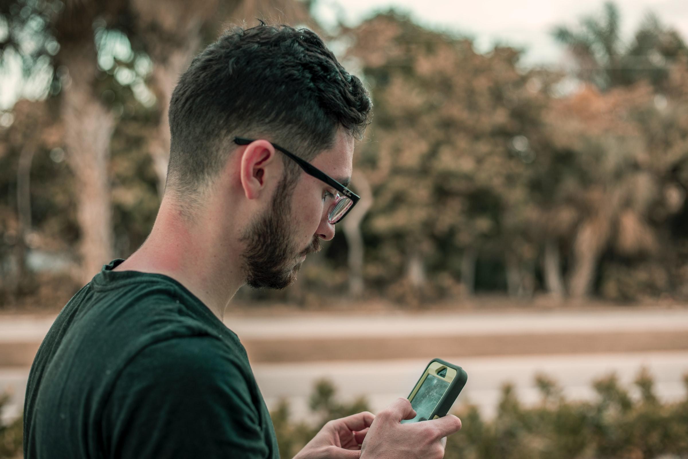 man läser på mobil