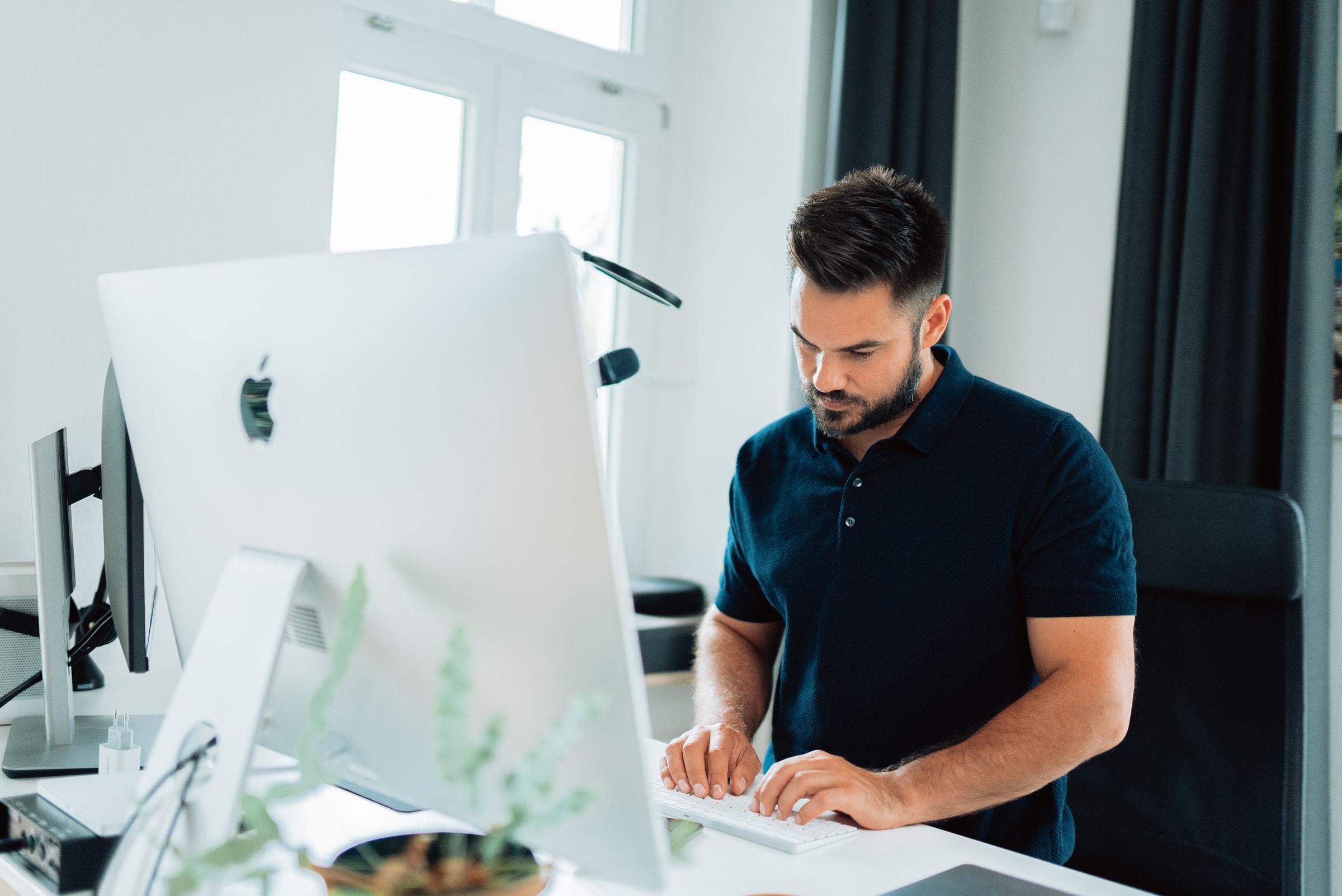 man står upp och jobbar framför dator