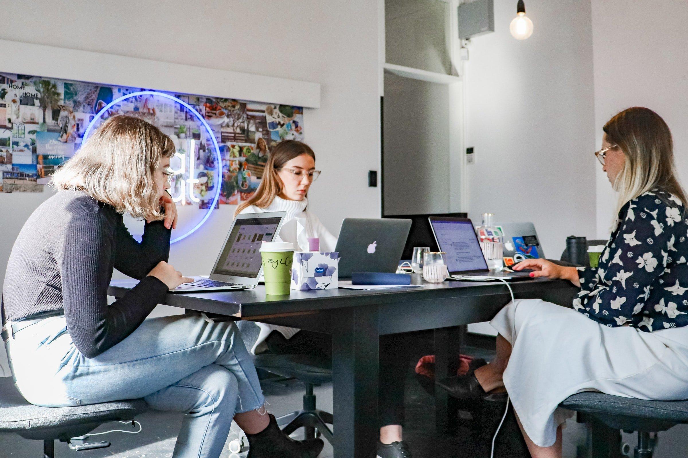 tre kvinnor samtalar runt konferensbord