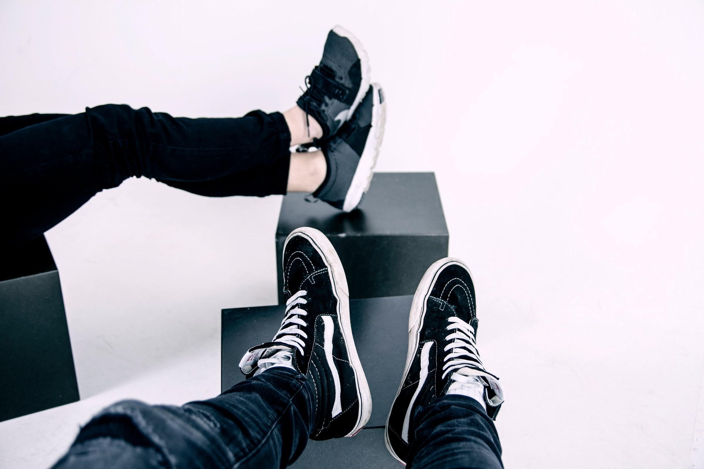 två olika par svarta sneakers