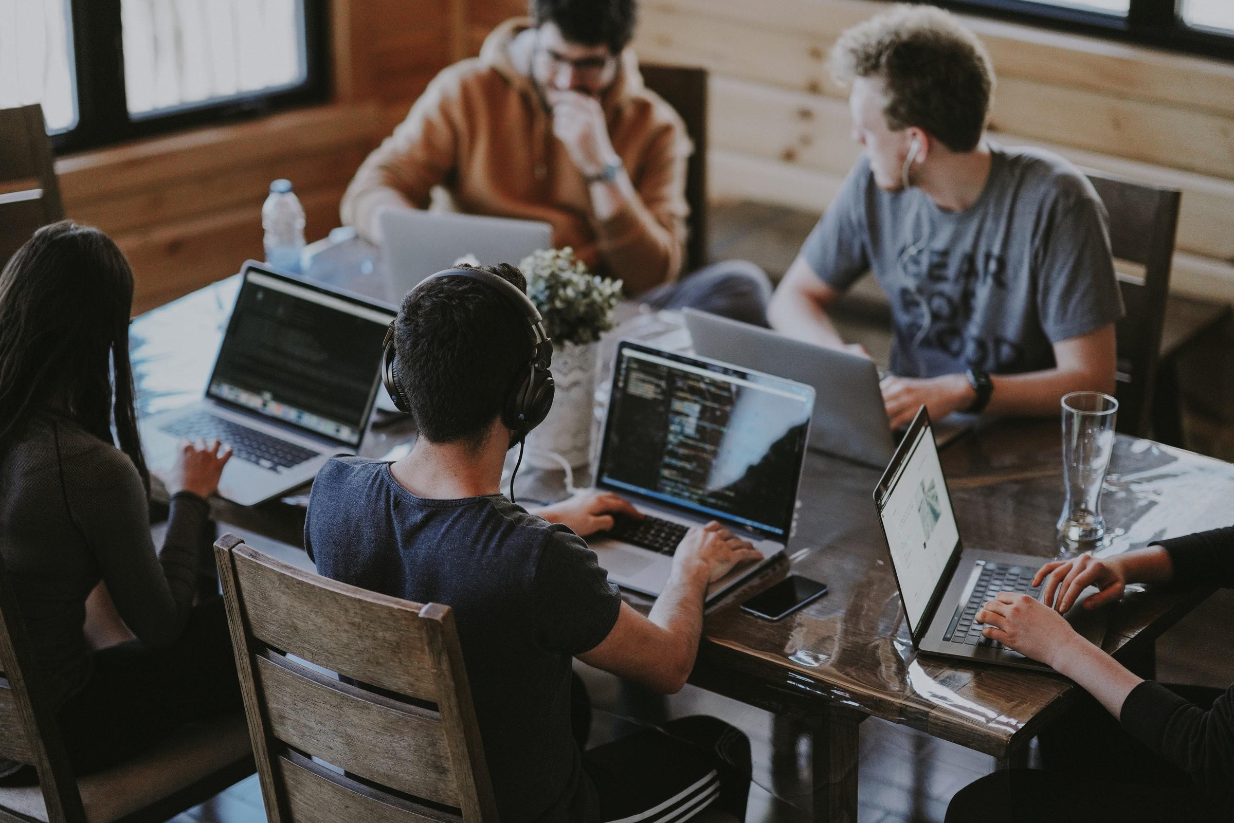 team arbetar tillsammans vid sina datorer