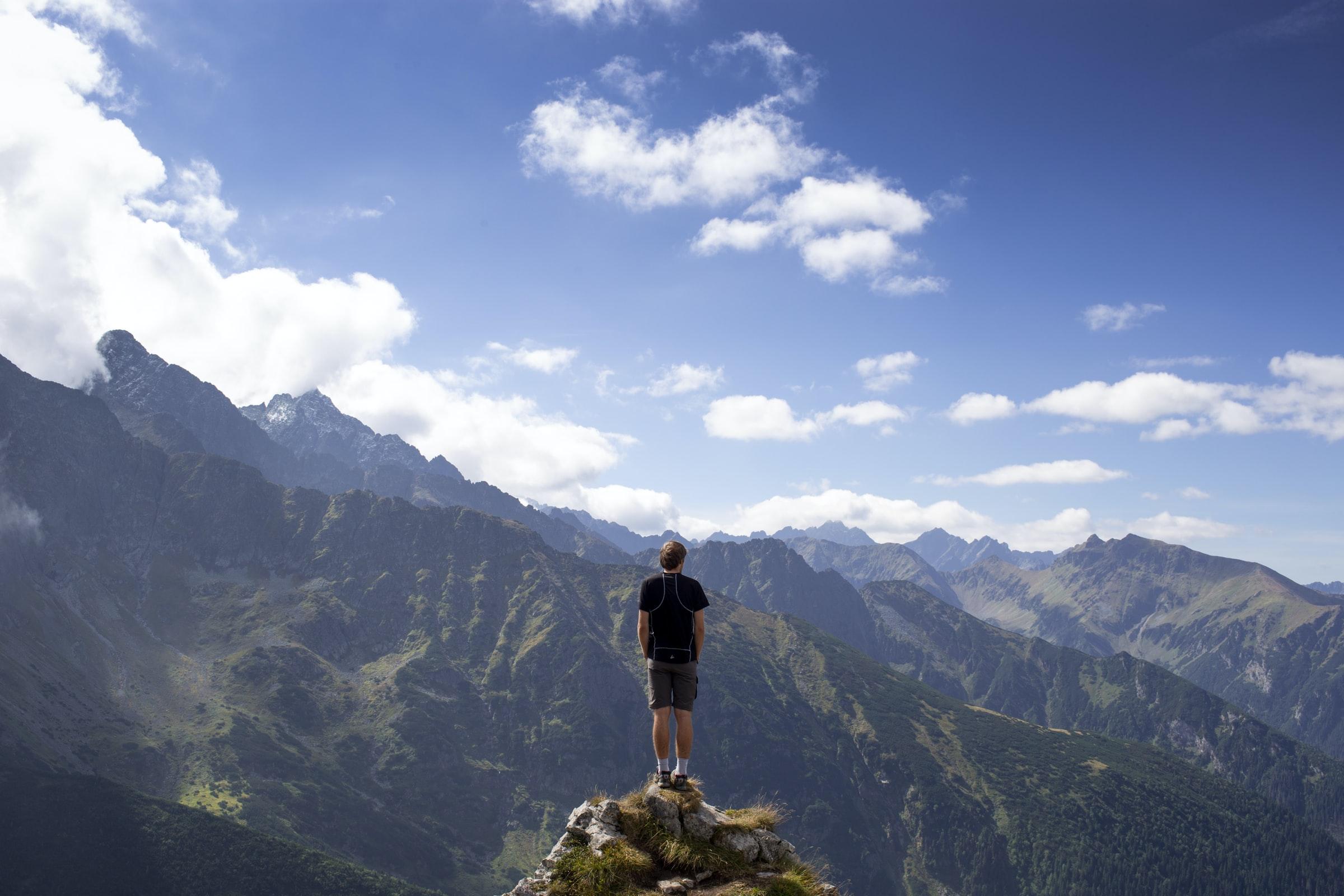 man som står på bergstopp och blickar ut