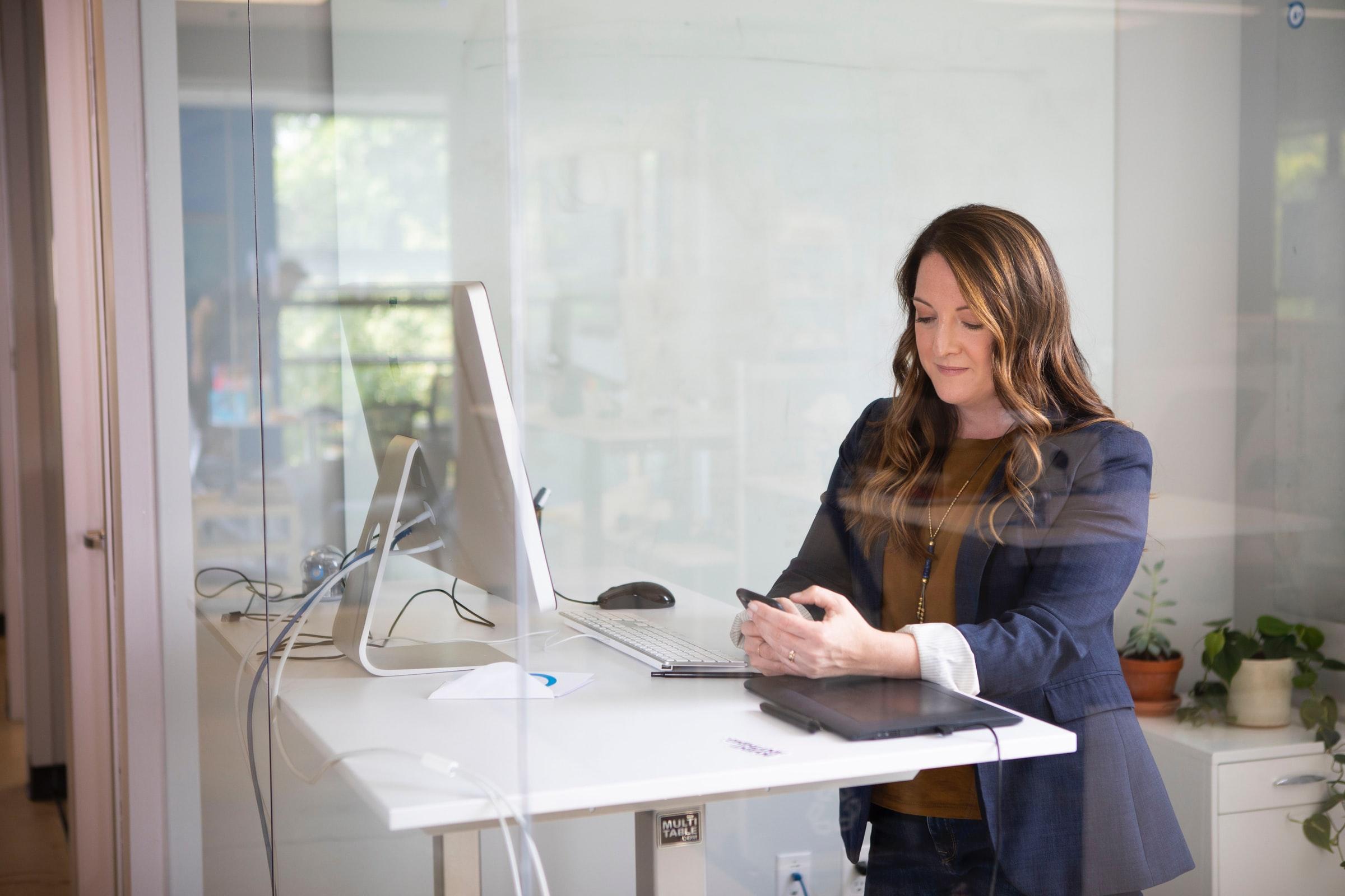 kvinna läser på mobil framför datorn
