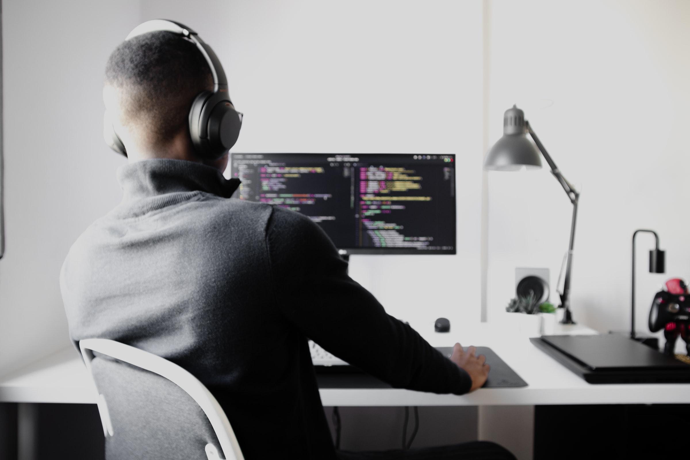 manlig systemutvecklare sitter framför dator