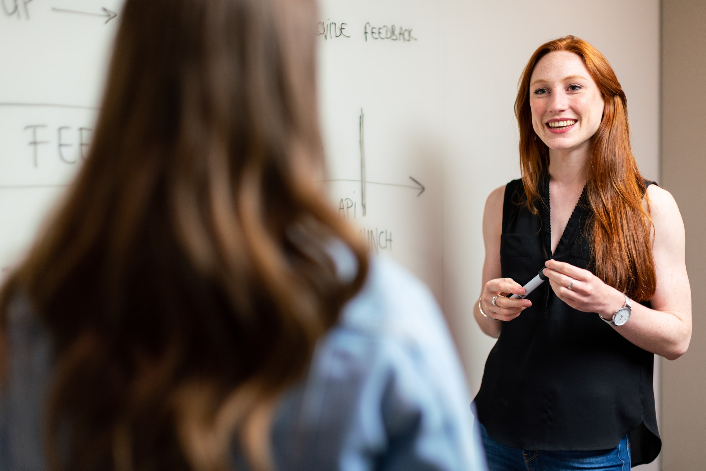 två kvinnor samtalar framför whiteboardtavla