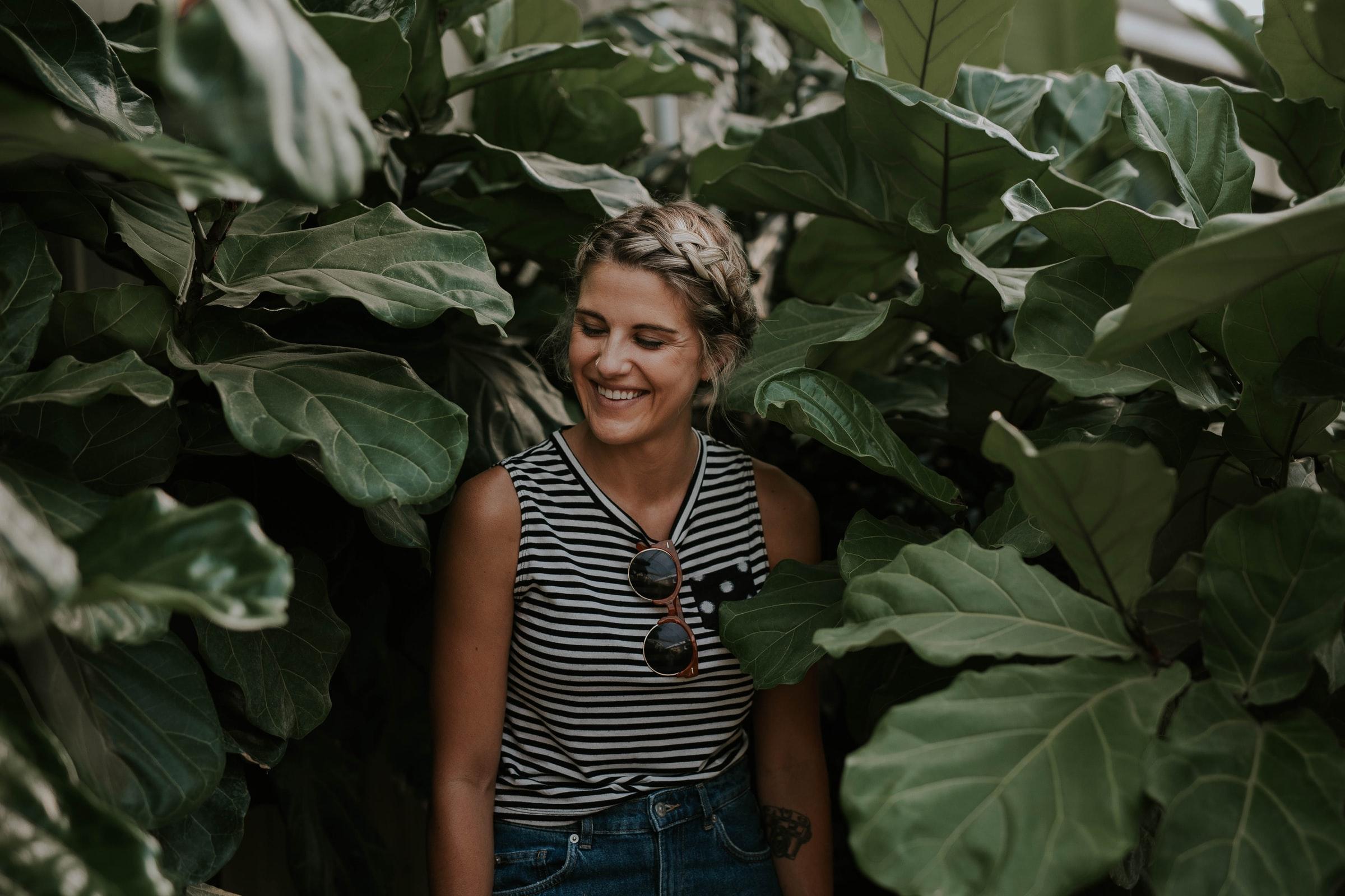 kvinna framför gröna löv