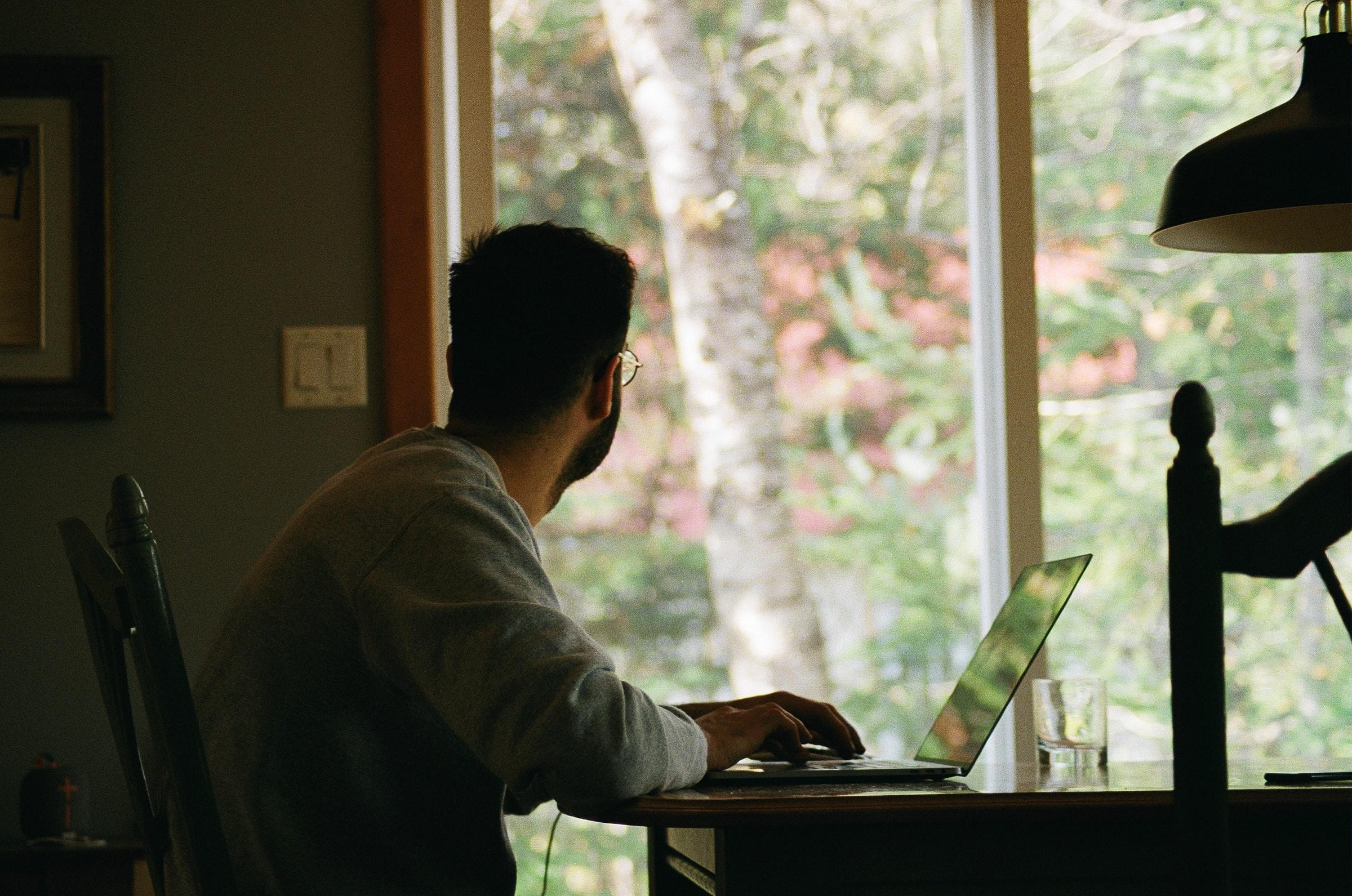 man framför dator vid fönster